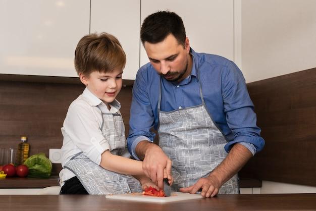 Niski kąt mały chłopiec w kuchni z ojcem