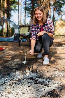 Niski kąt młoda kobieta gotowania marshmellow