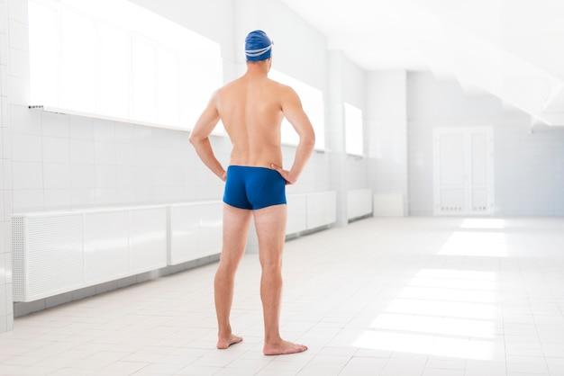 Niski kąt młody człowiek w basenie przygotowany do pływania