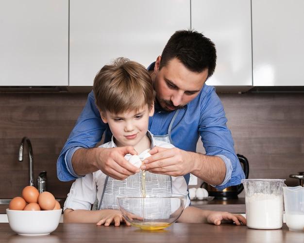 Niski kąt ojciec uczy syna roztrzaskiwać jajka