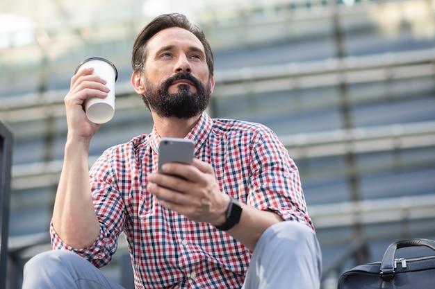 Niski kąt pewnego siebie brodatego mężczyzny pijącego kawę w środowisku miejskim