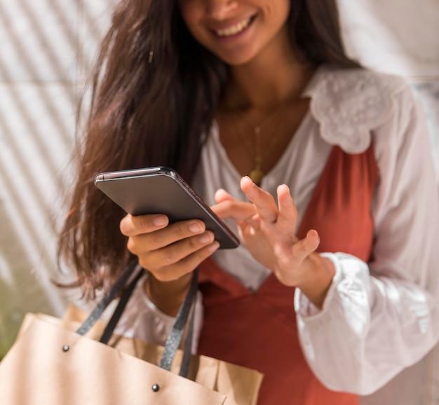 Niski kąt pięknej kobiety ze smartfonem