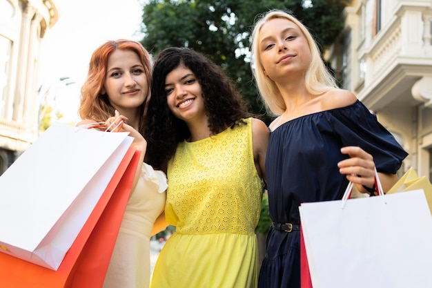 Niski kąt pięknych dziewczyn z torbami na zakupy