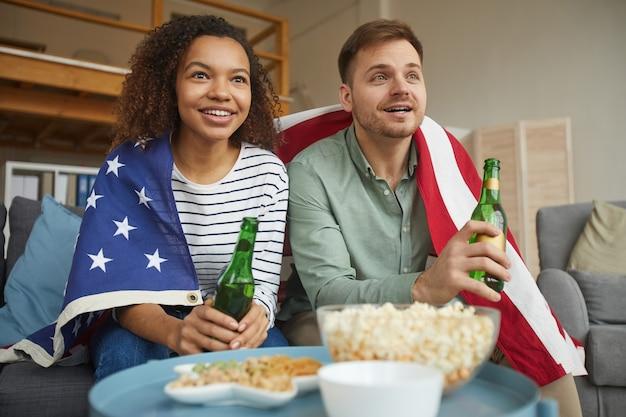 Niski kąt portret młodej pary rasy mieszanej, oglądając telewizję w domu i pijąc piwo, mając na sobie amerykańską flagę