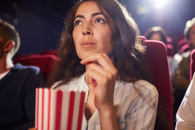 Niski kąt portret pięknej młodej kobiety jedzenie popcornu w kinie, oglądając sam film, patrząc na ekran