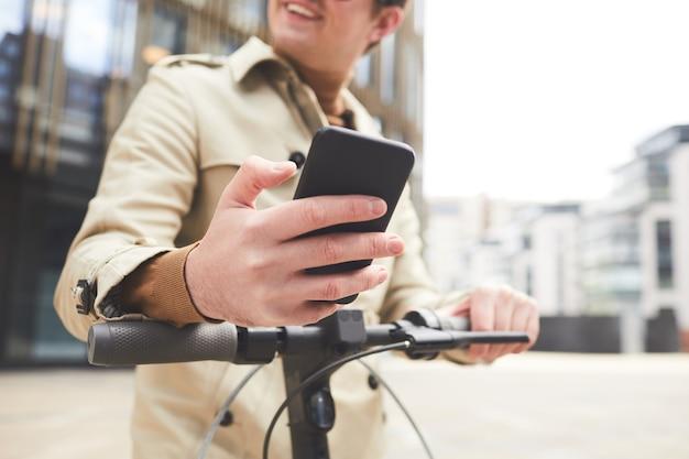 Niski kąt portret radosnego młodego mężczyzny w płaszczu odwracającym wzrok podczas korzystania ze smartfona i jazdy na skuterze elektrycznym z miejskimi budynkami miejskimi w tle, skup się na męskiej dłoni trzymającej telefon