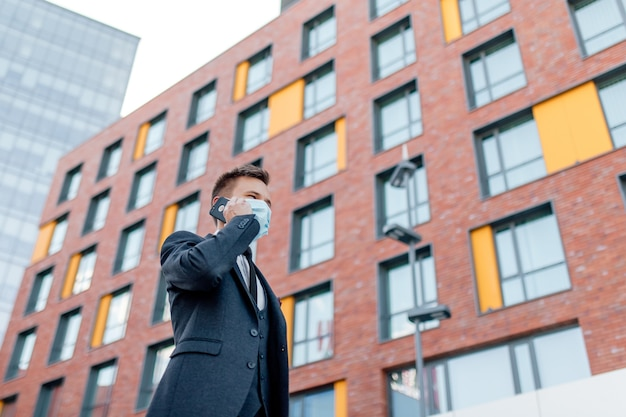 Niski kąt poważnego młodego przedsiębiorcy płci męskiej w formalnym garniturze i masce medycznej do zapobiegania koronawirusowi rozmawiającego na smartfonie, stojąc w centrum miasta