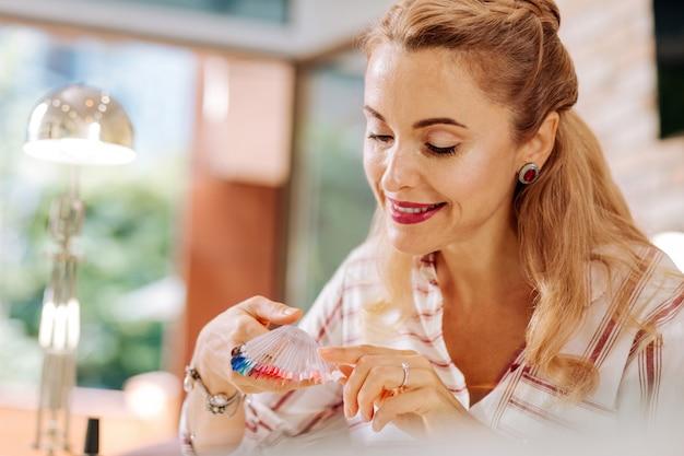 Niski kąt pozytywnej dojrzałej kobiety trzymającej próbki kolorów lakieru do paznokci i uśmiechającej się