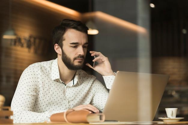 Niski kąt przedsiębiorca rozmawia przez telefon