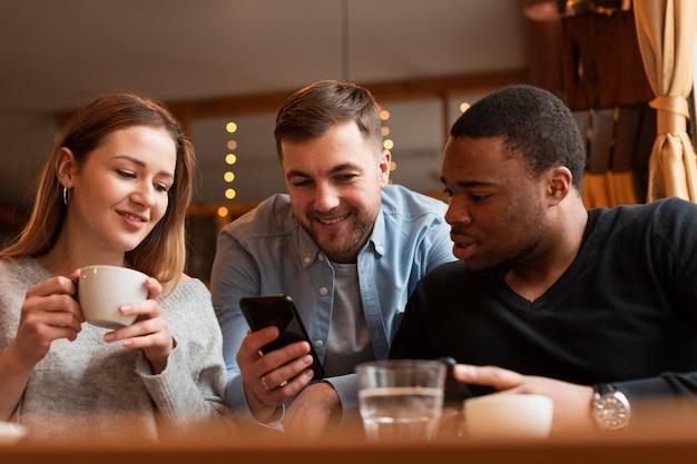 Niski kąt przyjaciół patrząc na telefon