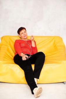 Niski kąt starsza kobieta na kanapie słuchania muzyki