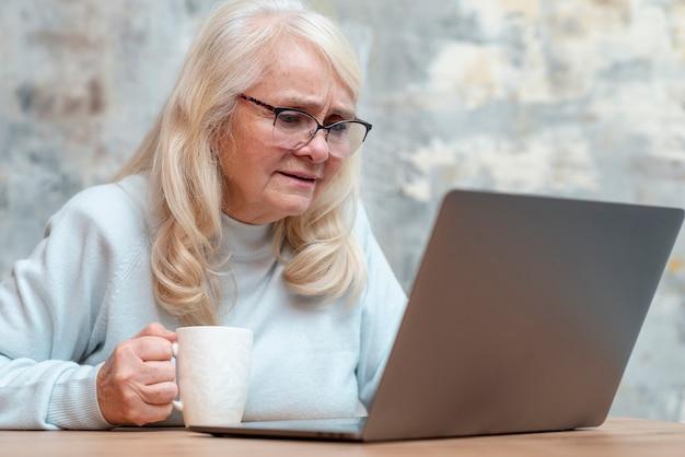 Niski kąt starsza kobieta za pomocą laptopa