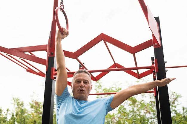 Niski kąt starszy mężczyzna ćwiczeń na świeżym powietrzu