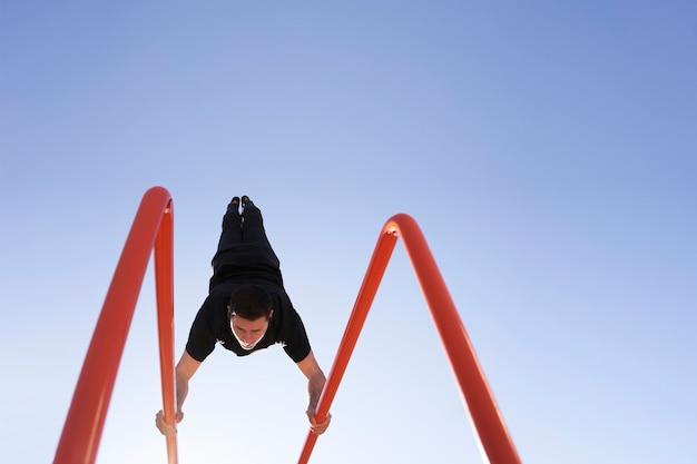 Niski kąt stojącego mężczyzny stojącego na sztangi w pionie. ćwiczenia na świeżym powietrzu. pojęcie zdrowego trybu życia, sportu, treningu, kalisteniki.