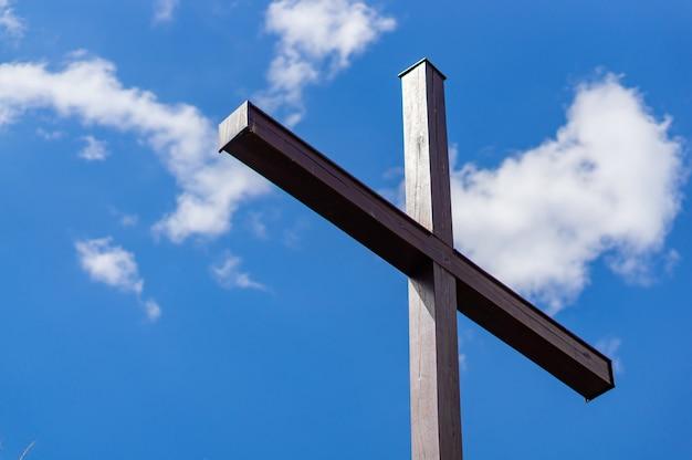 Niski kąt strzału drewnianego krzyża z pochmurnym niebieskim niebem