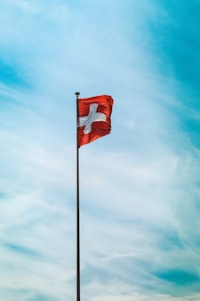 Niski kąt strzału flagi szwajcarii na słupie pod zapierające dech w piersiach pochmurne niebo