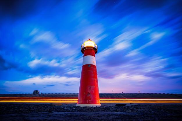 Niski kąt strzału latarni morskiej oświetlonej czerwono i biało na drodze pod niebieskim i fioletowym pochmurnym niebem