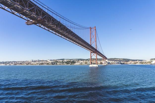Niski kąt strzału mostu ponte 25 de abril nad wodą z miastem w oddali