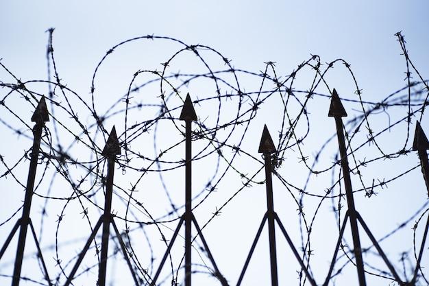 Niski kąt strzału ogrodzenia z drutu kolczastego pod jasnym, błękitnym niebem