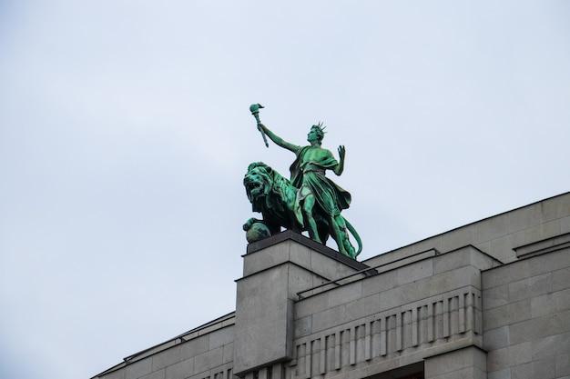 Niski kąt strzału posągu lwa na narodowym banku republiki czeskiej pod zachmurzonym niebem