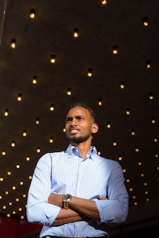 Niski kąt strzału przystojnego czarnego afrykańskiego biznesmena na zewnątrz w mieście latem, uśmiechnięty i myślący pionowy strzał