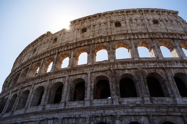Niski kąt strzału słynnego koloseum w rzymie, włochy pod jasnym niebem