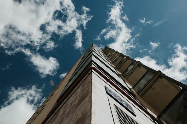 Niski kąt strzału wieżowca pod jasne błękitne niebo z białymi chmurami
