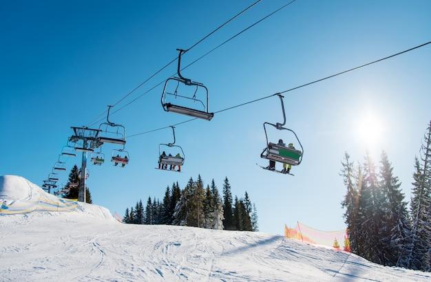 Niski kąt strzału wyciągu narciarskiego w ośrodku narciarskim bukovel w górach w słoneczny zimowy dzień