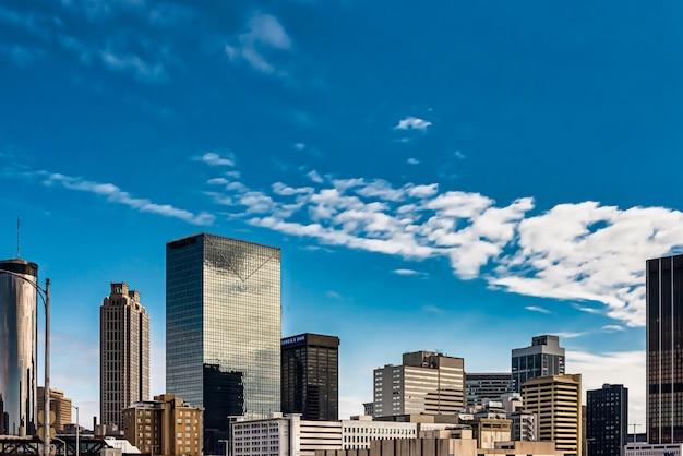 Niski kąt strzału wysokich szklanych budynków pod niebieskim pochmurnym niebem