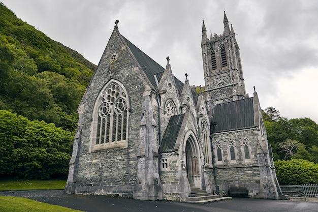Niski kąt strzału z kylemore abbey w irlandii, otoczony zielenią