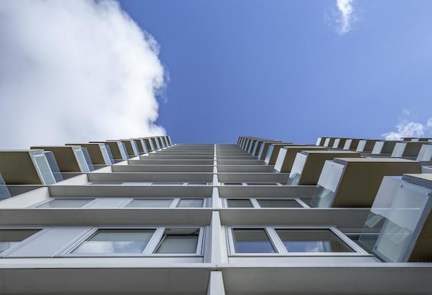 Niski kąt strzału z wysokiego białego budynku ze szklanymi balkonami pod jasnym błękitnym niebem