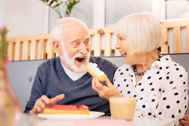 Niski kąt szczerej starszej kobiety trzymającej eclair i starszy mężczyzna ją połykając