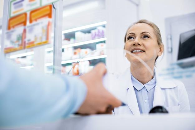 Niski kąt szczęśliwa farmaceuta kobieta uśmiecha się i rozmawia z człowiekiem