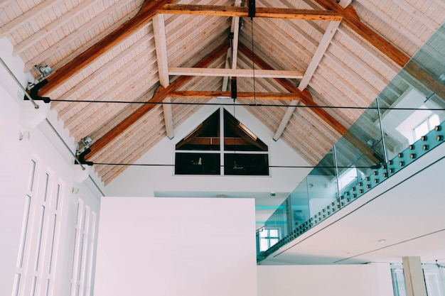 Niski kąt ujęcia drewnianego sufitu w chłodnym domu z nowoczesnym minimalistycznym wnętrzem