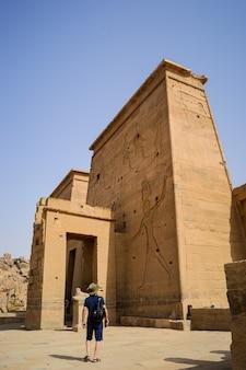 Niski kąt ujęcia mężczyzny stojącego przed świątynią izydy asuan w egipcie