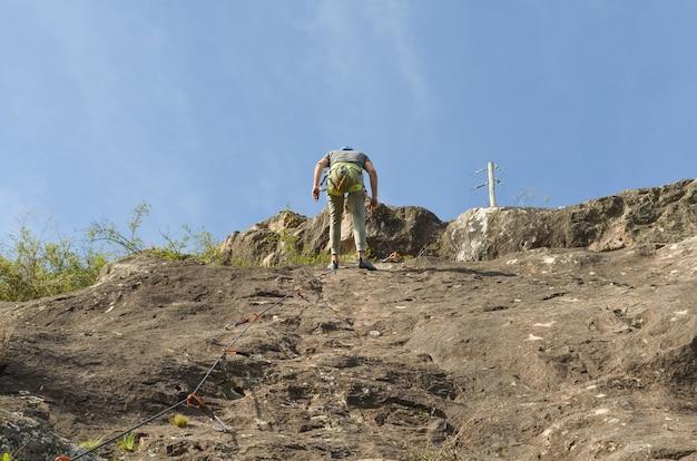 Niski kąt ujęcia młodego turysty wspinającego się po górach