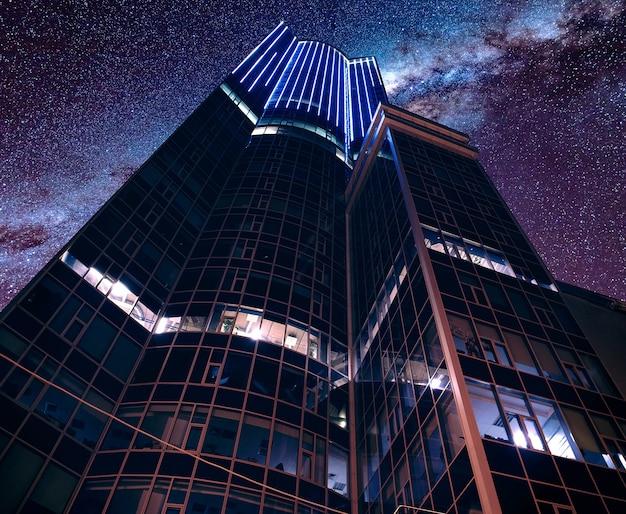 Niski kąt ujęcia nowoczesnej futurystycznej architektury biznesowej pod zapierającym dech w piersiach gwiaździstym niebem