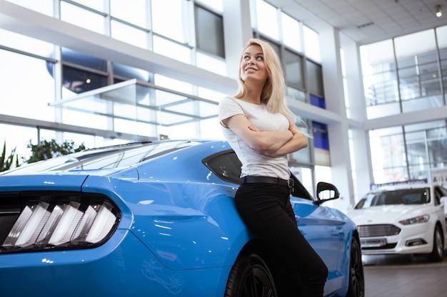Niski kąt ujęcia oszałamiającej kobiety kierowcy pozującej ze swoim nowym samochodem w salonie dealerskim.
