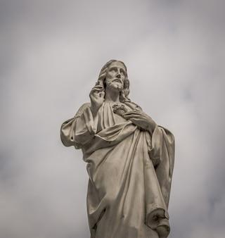 Niski kąt ujęcia posągu jezusa z uniesionymi palcami w pochmurny dzień