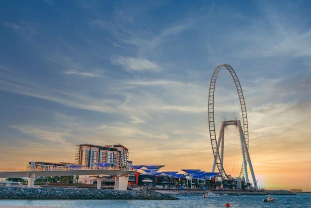 Niski kąt ujęcia przedstawiający nowoczesny projekt budynku z ogromnym diabelskim młynem na wyspie bluewaters w dubaju
