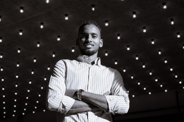 Niski kąt ujęcia przystojnego, udanego czarnego afrykańskiego biznesmena na zewnątrz w mieście latem, nakręcony w czerni i bieli