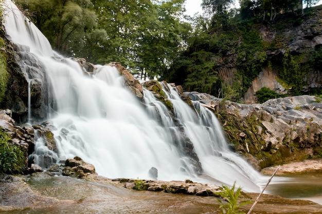 Niski kąt ujęcia skalistego wodospadu z zielonymi drzewami