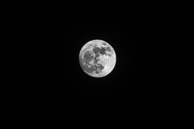 Niski kąt ujęcia zapierającego dech w piersiach księżyca w pełni uchwyconego na nocnym niebie