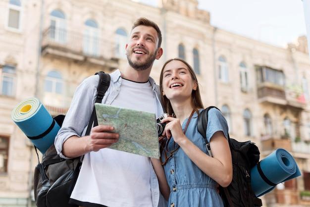 Niski kąt uśmiechniętej pary turystycznej z mapą