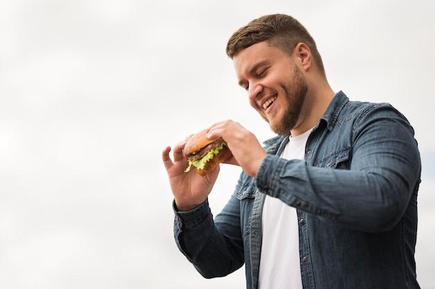 Niski kąt uśmiechnięty mężczyzna trzyma burgera