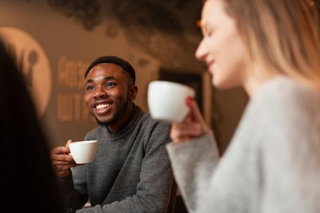 Niski kąt uśmiechniętych przyjaciół picia kawy