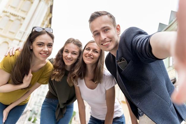 Niski kąt uśmiechniętych przyjaciół przy selfie