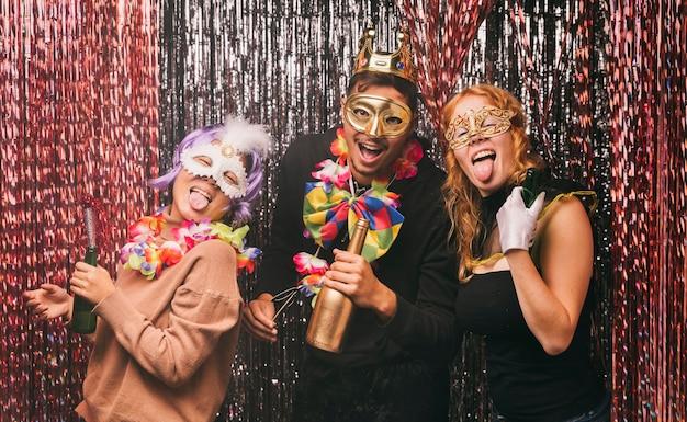 Niski kąt uśmiechniętych przyjaciół z kostiumami na imprezę karnawałową