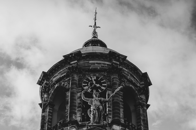 Niski kąt w skali szarości ujęcie pałacu królewskiego przy placu dam w amsterdamie, holandia