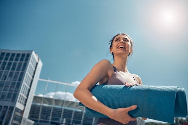 Niski kąt wesołej młodej kobiety trzymającej obiema rękami zwiniętą matę do jogi